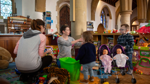 volunteer, young mum, and children at a play group