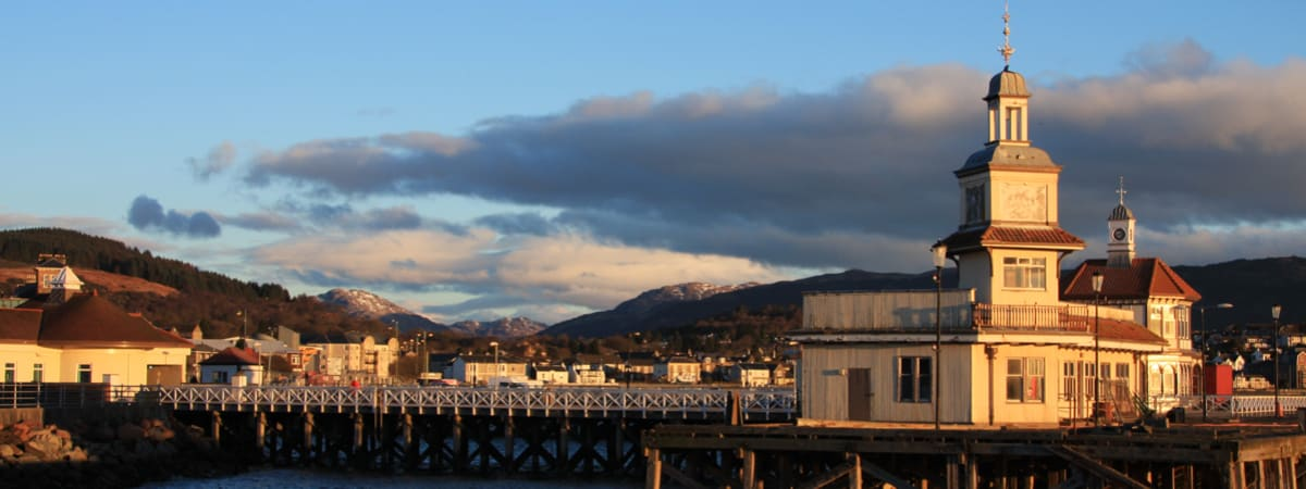 Pier in Dunoon with town and mountain in background.