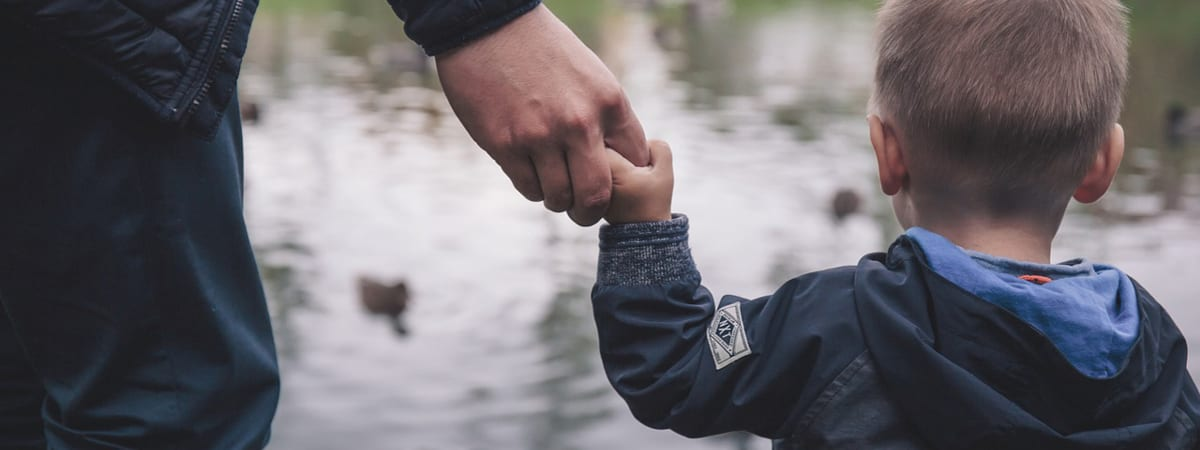 Man and child holding hands looking at a pond